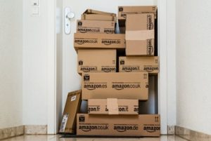 Boxes ordered online from amazon piled up in front of a door