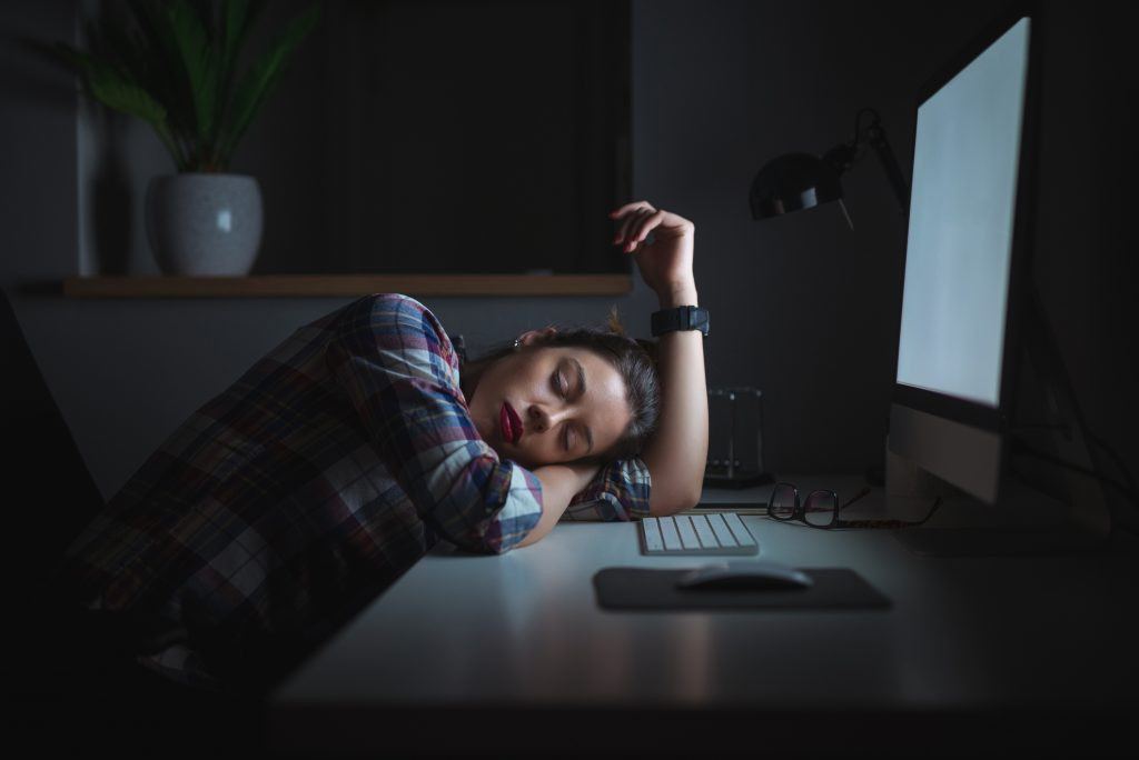 Shift worker asleep at her desk in front of her computer with the monitor still on
