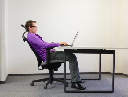 Office worker slouching in chair at desk with laptop, not in comfort