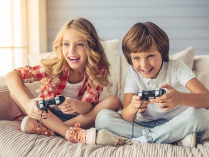 Kids playing video games, leaning forward not ergonomic gaming posture