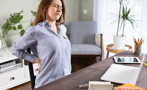 Woman in pain while at table working from home