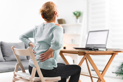 Woman in pain working at dining room table