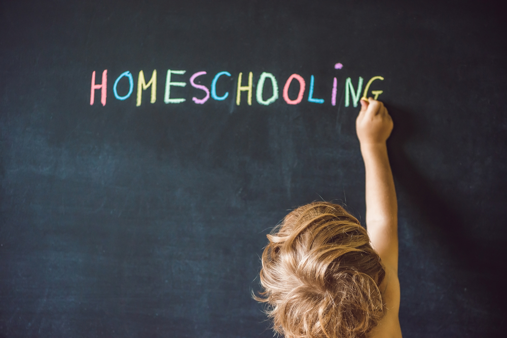 child writes homeschooling on blackboard