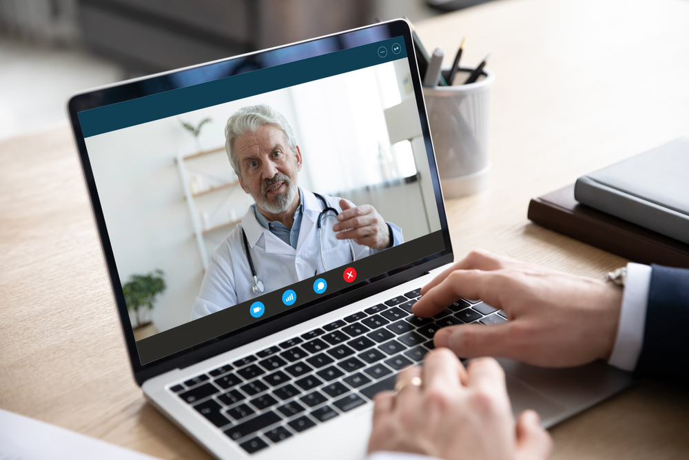 Physician on telehealth call laptop screen wellness champion