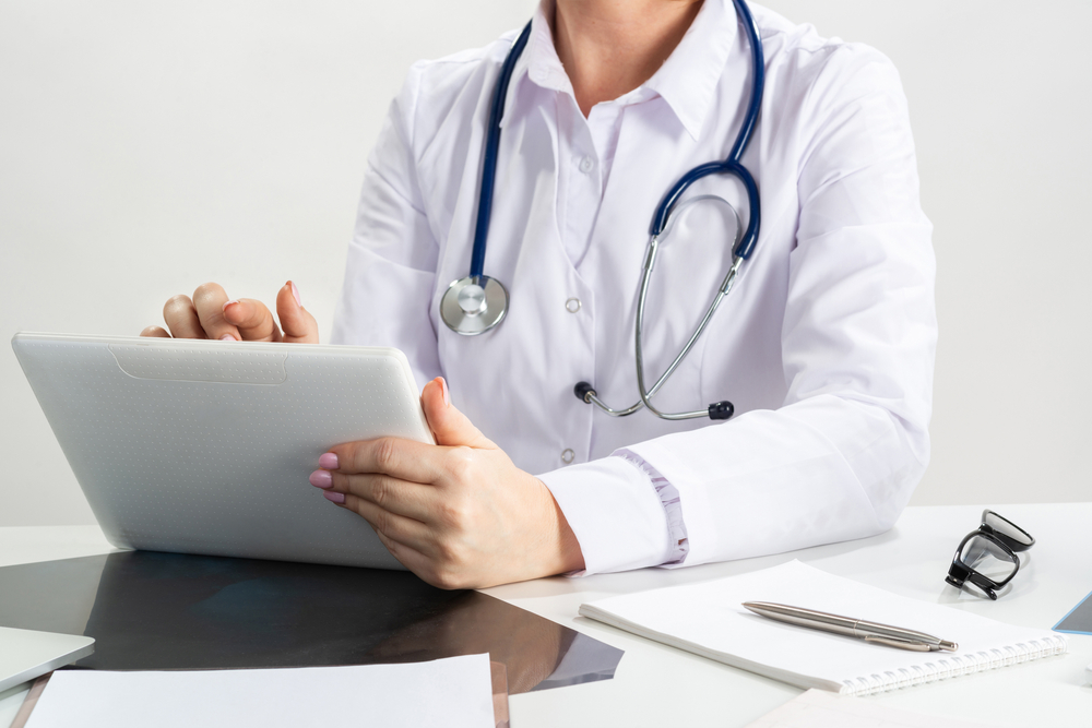 Wellness-Champion-Physician-entering-data-on-laptop